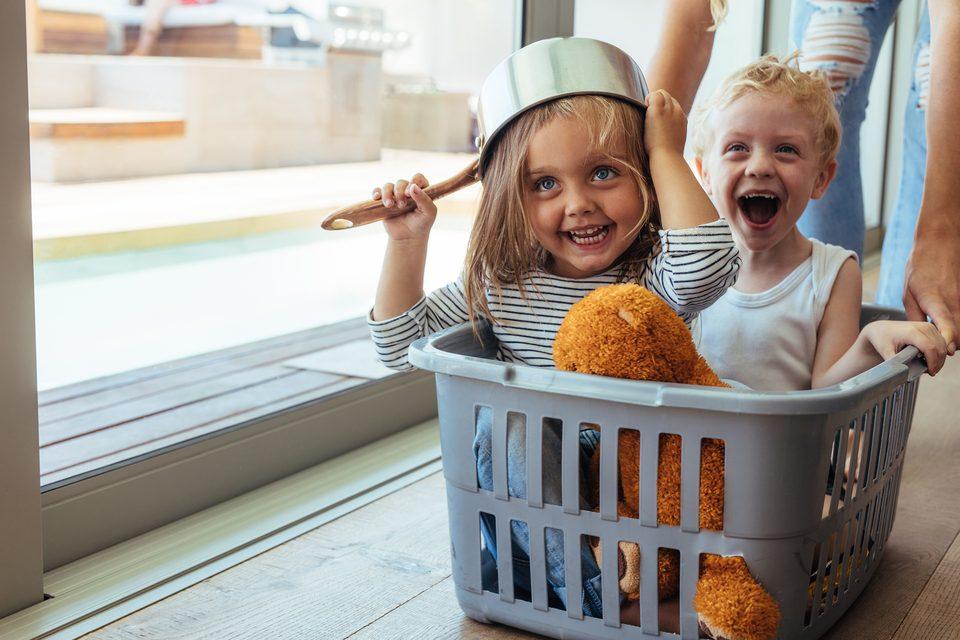Zwei Kinder in einem Wäschekorb