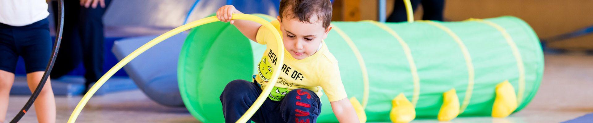 Teaser Kindertagespflege: Kind spielt mit Hula Hoop Reif