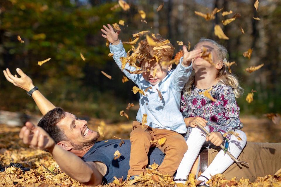 Vater spielt mit Kindern im Laub