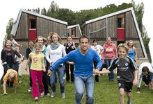 Sport- und Tagungszentren: Jugendgruppe vor Ferienhäusern