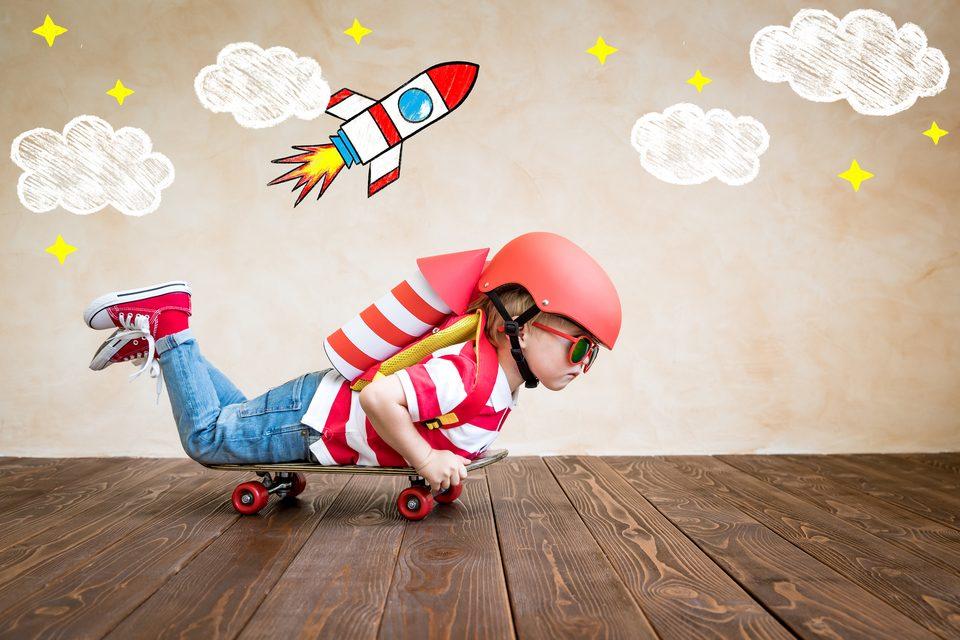 Kind auf einem Skateboard als Rakete verkleidet
