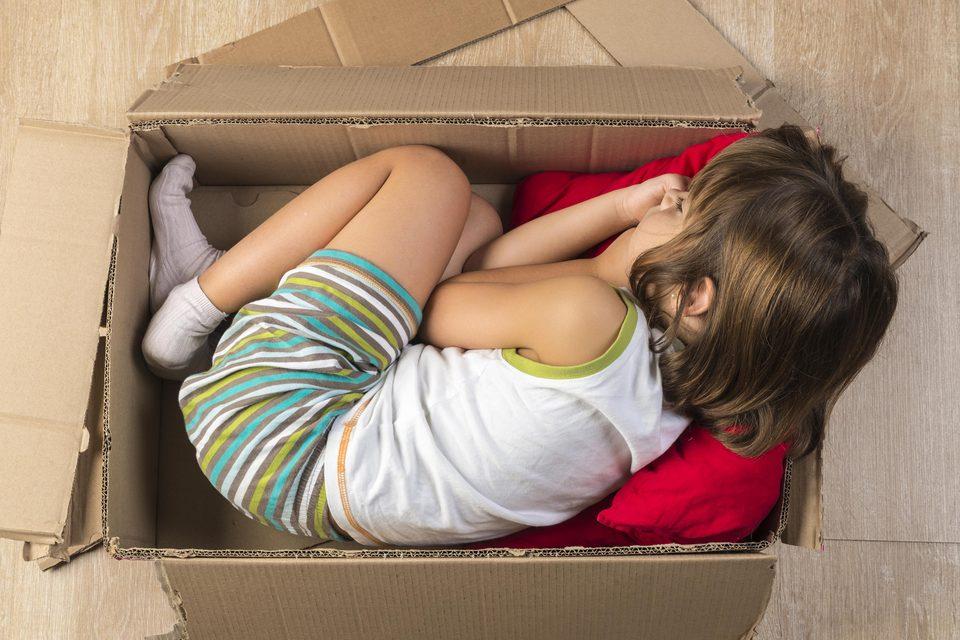 Mädchen liegt in einem Karton