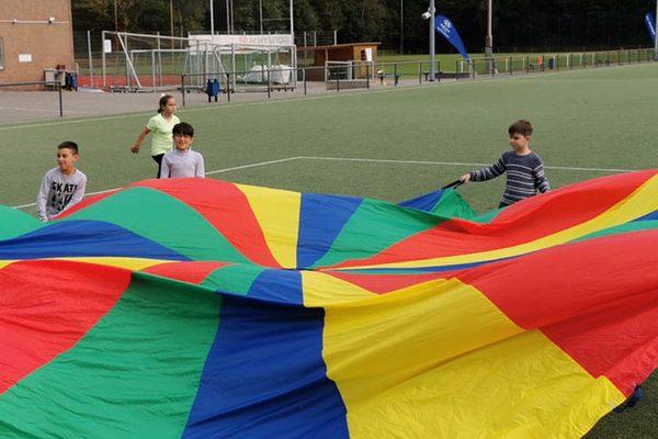 Kinder spielen mit dem Schwungtuch auf Sportplatz