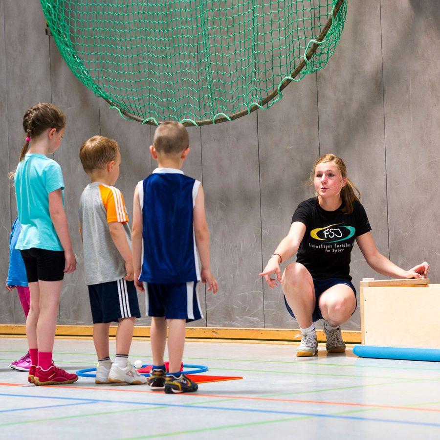 Kinder und Übungsleiterin in der Sporthalle