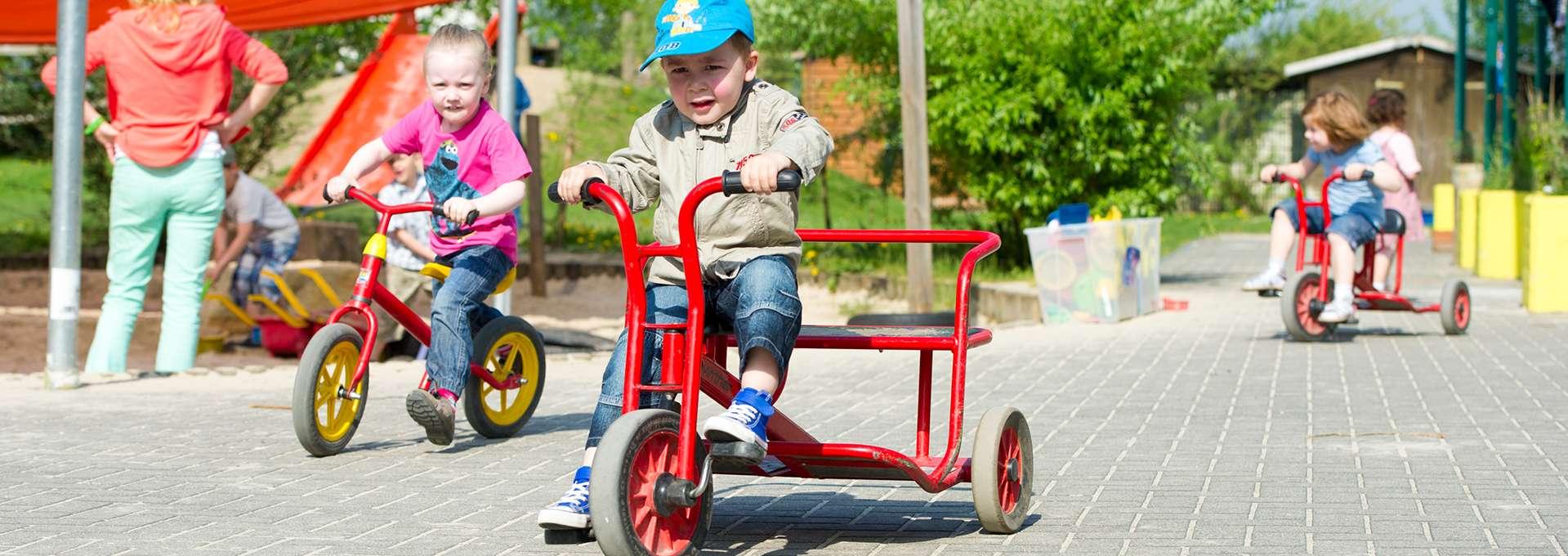 Headerbild Unser Engagement für Kinder: Kindergruppe mit Dreirädern